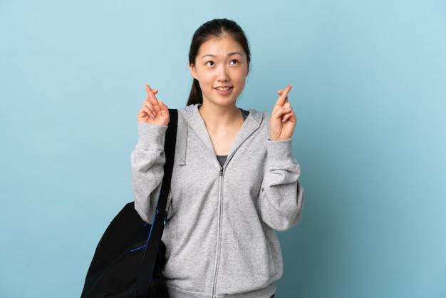 Giovane donna sportiva cinese con borsa sportiva sulla parete blu con le dita che attraversano e desiderano il meglio