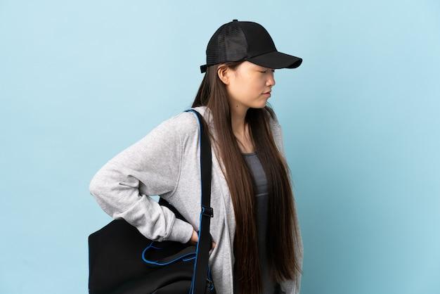 Giovane donna sportiva cinese con borsa sportiva su blu isolato sofferenza da mal di schiena per aver fatto uno sforzo