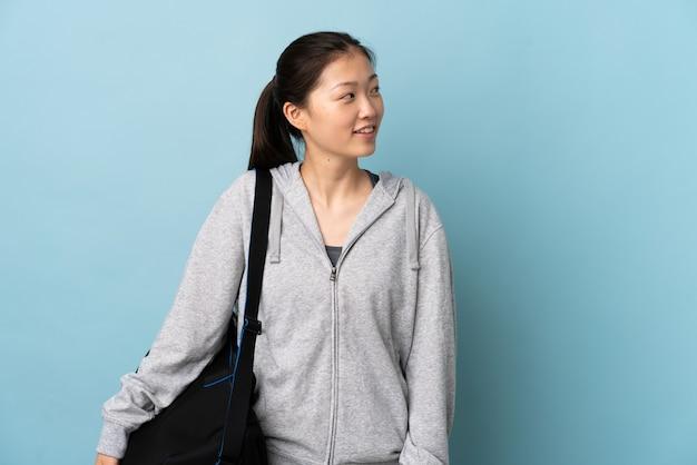 Giovane donna cinese di sport con la borsa di sport sopra la parete blu isolata che osserva al lato e che sorride
