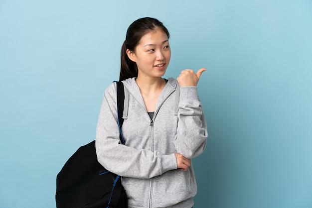 Giovane donna cinese di sport con la borsa di sport sopra la parete blu isolata che indica il lato per presentare un prodotto