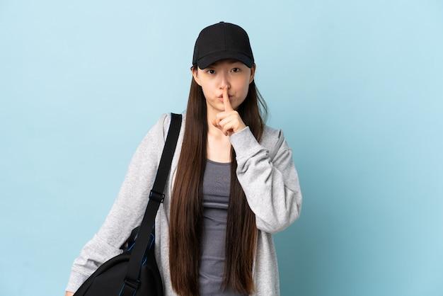 Donna cinese di giovane sport con la borsa di sport sopra la parete blu isolata che mostra un segno di gesto di silenzio che mette il dito in bocca