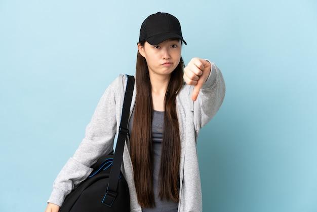 Giovane donna cinese di sport con la borsa di sport sopra la parete blu isolata che mostra il pollice giù con l'espressione negativa
