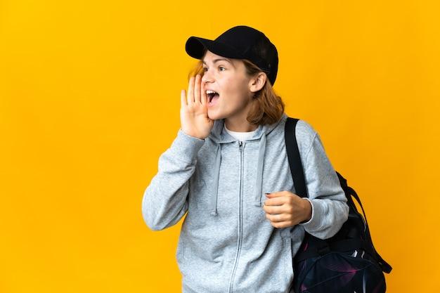 Young sport donna georgiana con borsa sportiva su sfondo isolato gridando con la bocca spalancata di lato