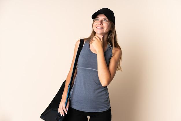 Giovane donna lituana di sport che tiene una borsa di sport isolata su fondo beige che osserva in su mentre sorride