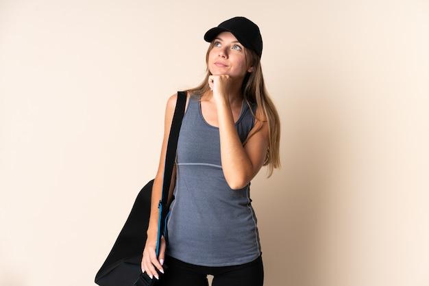 Giovane donna lituana di sport che tiene una borsa sportiva isolata su fondo beige e che osserva in su