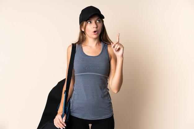 Giovane donna lituana di sport che tiene una borsa di sport isolata su fondo beige che pensa un'idea che indica il dito verso l'alto