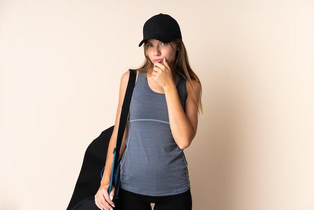 Giovane donna lituana di sport che tiene una borsa di sport isolata sul pensiero beige del fondo