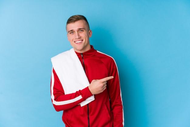 Giovane uomo di sport che sorride e che indica da parte, mostrando qualcosa nello spazio vuoto.