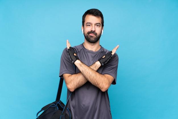 Giovane uomo di sport con la barba sopra il blu che non fa gesto