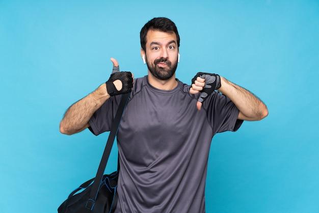 Giovane uomo di sport con la barba sopra il segno buono-cattivo di fabbricazione blu isolato. indeciso tra sì o no