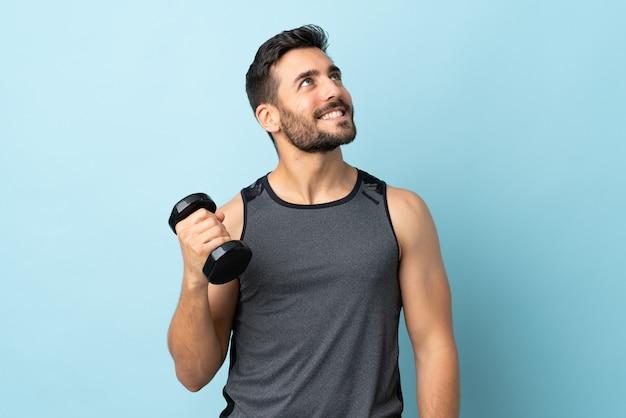 Giovane uomo di sport con la barba che fa sollevamento pesi alzando lo sguardo mentre sorride