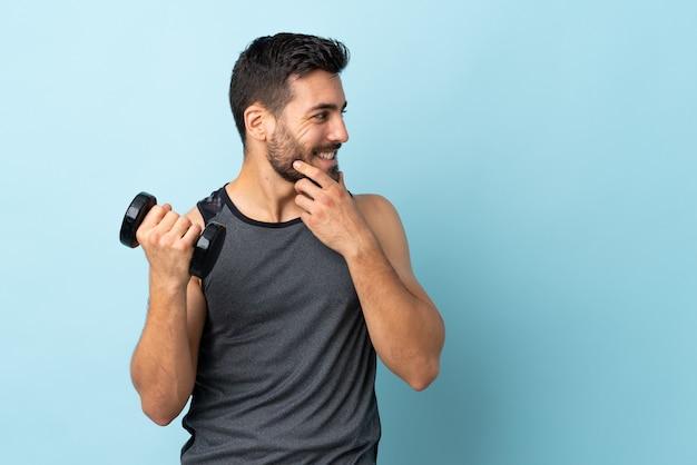 Giovane uomo di sport con la barba che fa sollevamento pesi pensando un'idea e guardando di lato