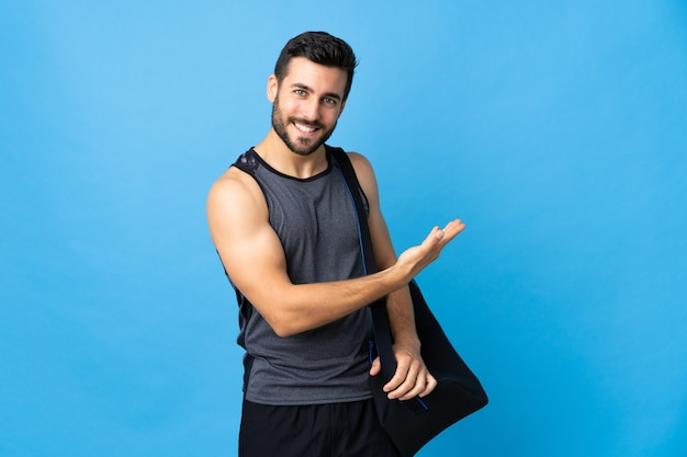 Giovane uomo di sport con borsa sportiva isolata sull'azzurro che presenta un'idea mentre guarda sorridente verso