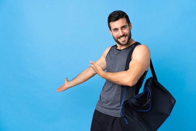 Giovane uomo di sport con borsa sportiva isolata sulla parete blu che estende le mani a lato per invitare a venire