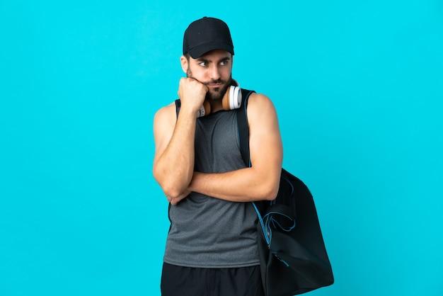 Giovane uomo di sport con borsa sportiva isolato su blu con espressione stanca e annoiata