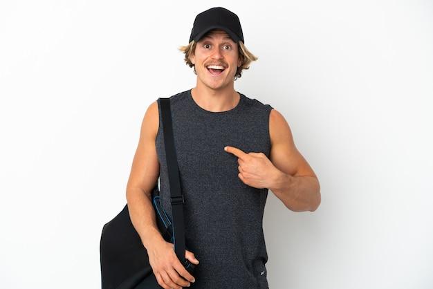 Giovane uomo sportivo con borsa sportiva isolato su sfondo bianco con espressione facciale a sorpresa