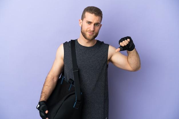 Giovane uomo di sport con borsa sportiva isolato su bianco che mostra il pollice verso il basso con espressione negativa
