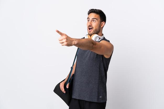 Giovane uomo di sport con borsa sportiva isolato sul muro bianco che punta lontano