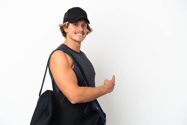 Giovane uomo di sport con borsa sportiva isolata sulla parete bianca che indica indietro