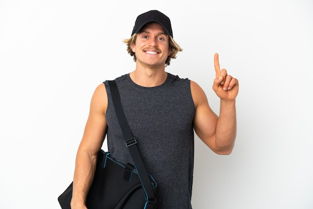 Giovane uomo di sport con borsa sportiva isolato sul muro bianco rivolto verso l'alto una grande idea