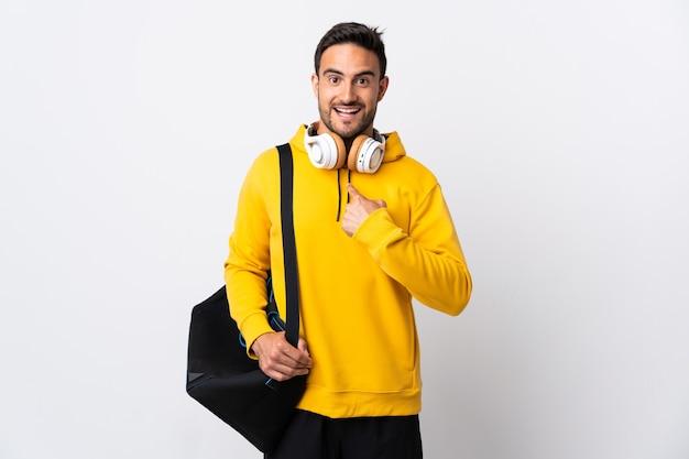 Giovane uomo di sport con borsa sportiva isolato sul muro bianco con espressione facciale a sorpresa