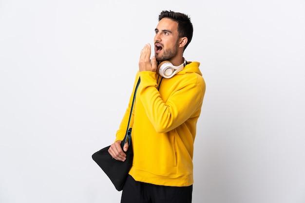 Giovane uomo di sport con borsa sportiva isolata sul muro bianco che sbadiglia e che copre la bocca spalancata con la mano