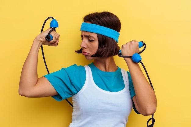 Young sport donna di razza mista che tiene una corda elastica isolata su sfondo giallo