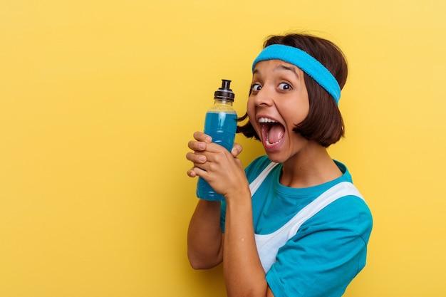 Giovane donna di razza mista sport isolata bere una bevanda energetica su sfondo giallo