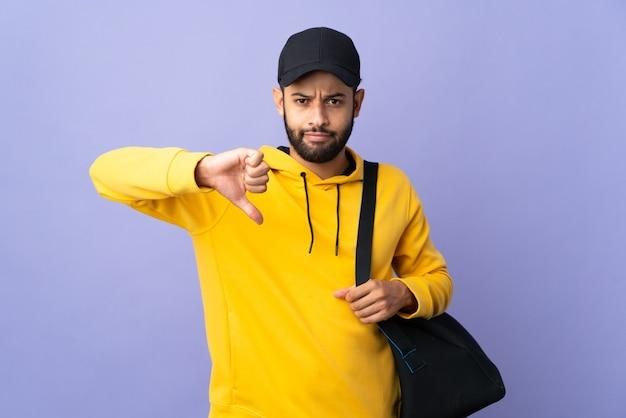 Young sport uomo marocchino con borsa sportiva isolato su sfondo viola che mostra il pollice verso il basso con espressione negativa