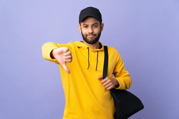 Giovane uomo marocchino di sport con borsa sportiva isolato sulla parete viola che mostra il pollice verso il basso con espressione negativa