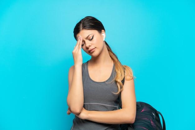 Giovane ragazza russa sportiva con borsa sportiva isolata su sfondo blu con mal di testa