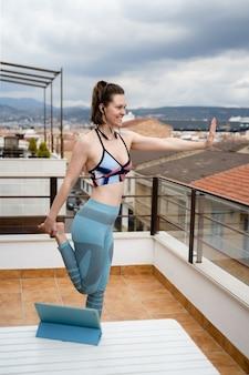 Giovane donna di sport che fa allenamento online a casa