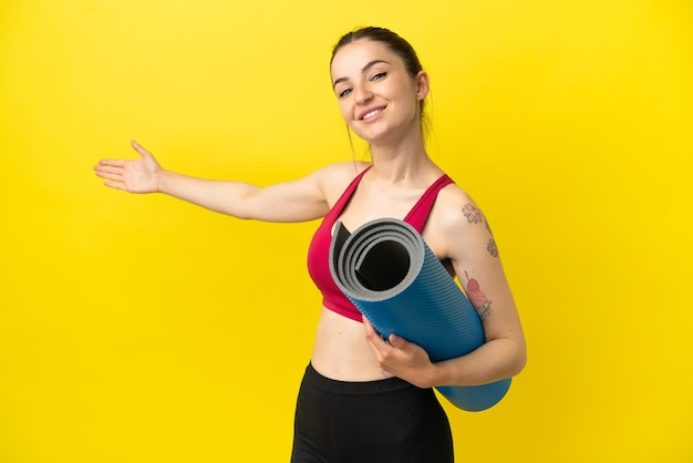 Giovane donna sportiva che va alle lezioni di yoga tenendo un tappetino che allunga le mani ai lati per invitare a venire