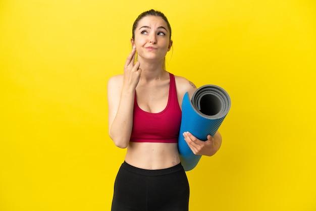 Giovane donna sportiva che va alle lezioni di yoga tenendo in mano un tappetino con le dita incrociate e augurando il meglio