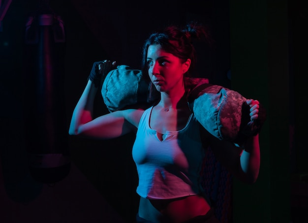 Giovane donna sportiva che tiene una borsa fitness pesante per allenamento in luce rossa blu sfumata al neon su un muro scuro concetto di allenamento funzionale