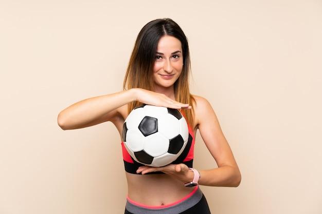 Giovane donna di sport sopra la parete isolata che tiene un pallone da calcio