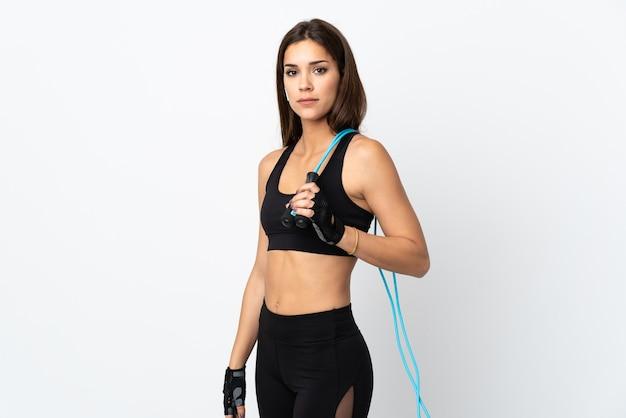 Giovane donna sportiva isolata su sfondo bianco con salto con la corda