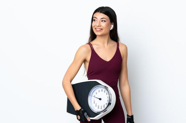 Giovane donna di sport sopra la parete bianca isolata con la pesa
