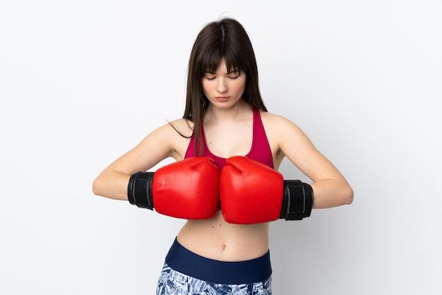 Giovane donna sportiva isolata su bianco con guantoni da boxe