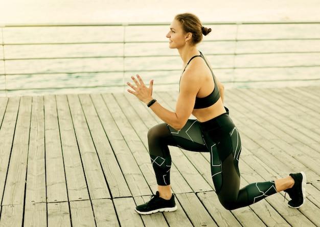 La giovane donna sportiva si lancia sulla terrazza della spiaggia