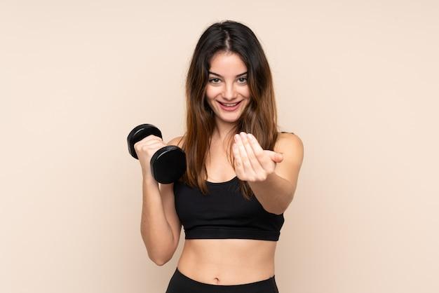 Giovane donna di sport che fa sollevamento pesi isolato sull'invito beige a venire