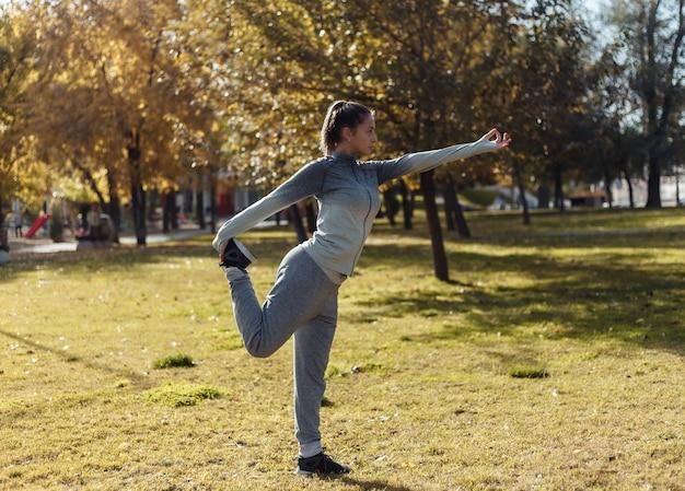 Giovane donna di sport che praticano esercizi di asana yoga nella sosta di autunno