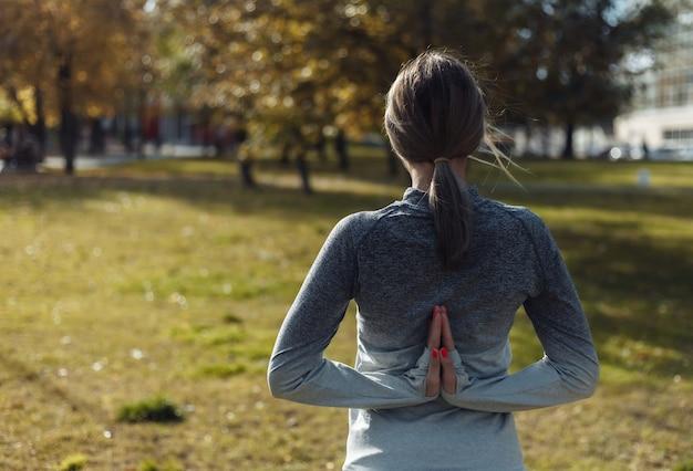 Giovane donna sportiva a praticare yoga namaste da dietro nel parco