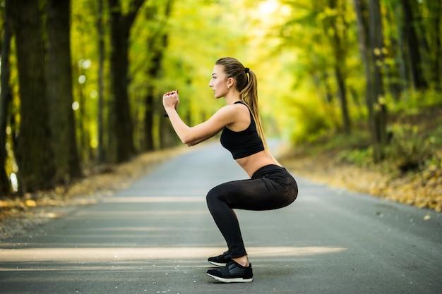 Il corridore della giovane donna sportiva si riscalda all'aperto