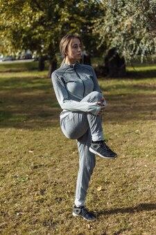 La giovane donna sportiva in una tuta sportiva si sta riscaldando nel parco in autunno