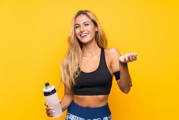 Giovane donna di sport con una bottiglia di acqua sopra isolata
