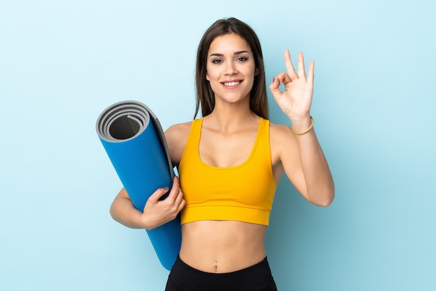 Giovane donna sportiva con la stuoia sul blu che mostra segno giusto con le dita