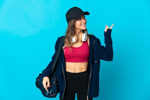 Giovane donna sportiva con borsa sportiva sul blu rivolto verso l'alto una grande idea