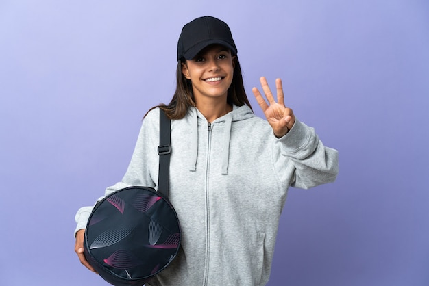 Giovane donna sportiva con borsa sportiva felice e contando tre con le dita