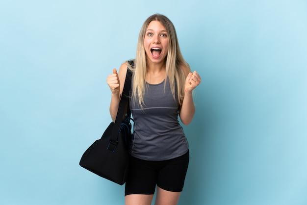 Giovane donna di sport con la borsa di sport isolata sulla parete blu che celebra una vittoria nella posizione del vincitore